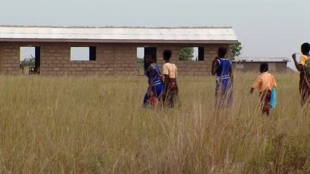 africký : Wide shot of kids walking through field with shcoolhouse in background Dostupné videozáznamy