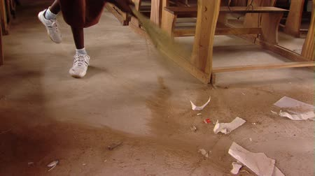 бедный : Close up shot of girl sweeping out classroom