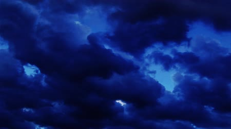 bulutluluk : Time-Lapse of dark clouds at dusk roll left across a deep blue sky. Stok Video