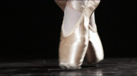 balerína : Close up of a pair of feet in ballet shoes with a black background