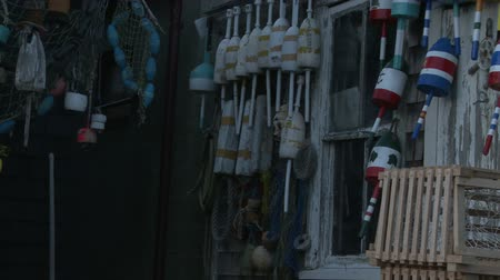 gaiola : Slow pan of fishing buoys hanging on the walls with nets, buoys, and cages at a weathered fishing shack in Rockport, Massachusetts. Stock Footage