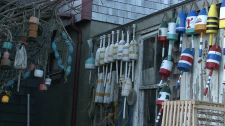 kafes : Slow pan of fishing buoys hanging on the walls with nets, buoys, and cages at a weathered fishing shack in Rockport, Massachusetts. Stok Video