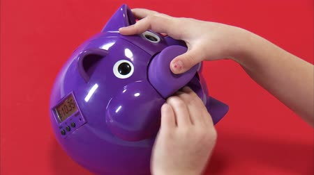 pieniądze : A close static shot from above of an eight year old girl putting money in her piggy bank on white.
