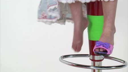 sapato : A close up shot on white of a little girl playing on a tall chair and kicking off her shoes.