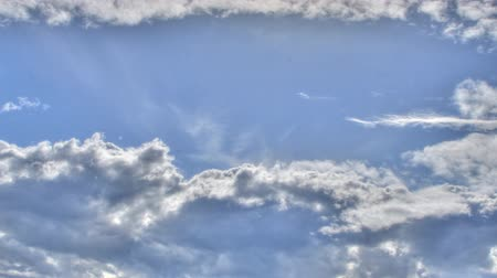 небесный : Timelapse of fluffy white clouds move forward in a power-blue sky.