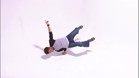 descanso : A wide shot of a break dancer doing a hand stand on a white screen. Stock Footage