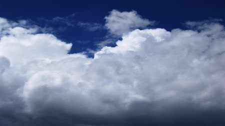 mroczne : Timelapse of white clouds roll across a dark blue sky.