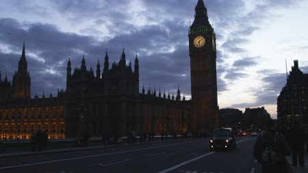 zegar : Wide shot silhouette of Big Ben at dusk with traffic passing by