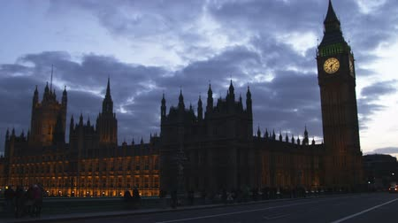 парламент : Wide shot silhouette of Big Ben at dusk with traffic passing by