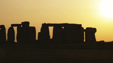 earthworks : Wide shot pan of Stonehenge at sunset