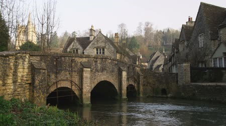 grzebień : Wide shot pan of old stone village and bridge over stream