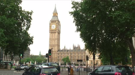 big ben : View of Big Ben clock tower between trees as cars pass in London, England. Stock Footage