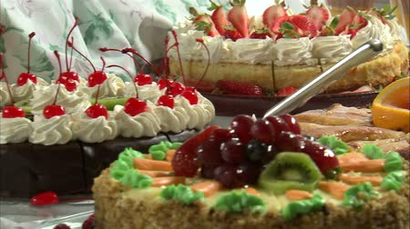 буфет : Close-up move across delicious looking desserts on a table. There are cakes, pies, fruit, and other colorful treats. Стоковые видеозаписи