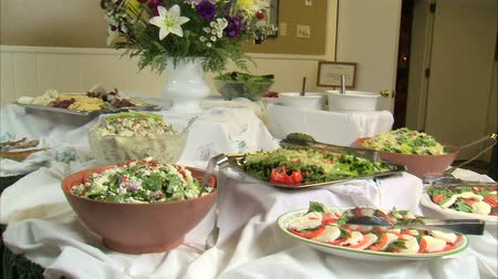 salad : Table full of serving bowls with delicious-looking salads, vegetables, and other food.