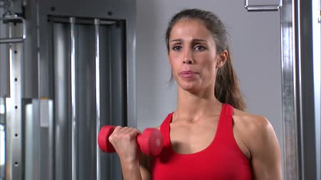 súlyzó : A woman doing arm curls with a pair of dumbbells Stock mozgókép