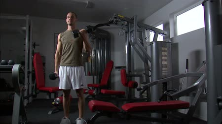 súlyzó : A man doing arm curls with a pair of dumbbells Stock mozgókép