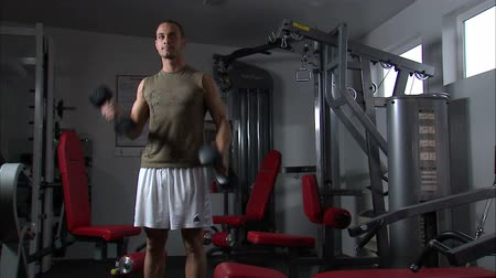 enrolar : A man doing arm curls with a pair of dumbbells Stock Footage