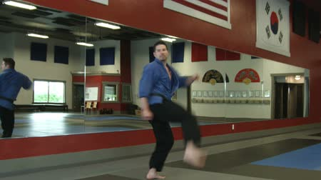 каратэ : Male martial artist doing a spin kick wearing a blue gi in a martial arts studio