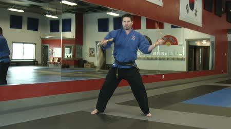 каратэ : Slow rotating shot of a man in a karate studio practicin nunchuck weapon moves Стоковые видеозаписи