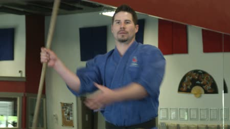 каратэ : Man in martial art gear spnning a bow staff around practicing moves
