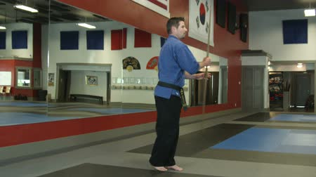 каратэ : Man in a karate studio does bod staff moves, inlcuding spinning at different angles and throwing and catching