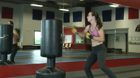 puncs : Female does punch kick combos on a padded self standing punching bag in a gym Stock mozgókép