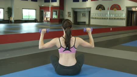 bicep : Back shot of a female sitting on the ground lifting weights overhead in a gym