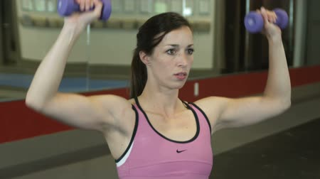 fitnes : Close up rotating shot of a female in a gym lifting weights