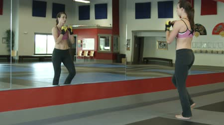 defesa : Full body shot of a female warming up in a gym practing kicks in the mirror
