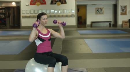 gyönyörű nő : woman in a gym sitting on a workout ball doing arm workouts