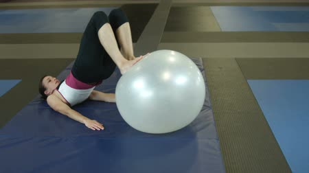 súlyzó : Woman in a gym lying on the floor doing leg workout with an exercise ball