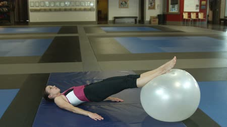 ćwiczenia : Girl in a gym does leg lifts with a fitness ball under her feet while lying on the floor