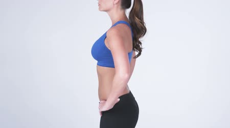 fitnes : Left side view panning shot down of a white female against a white background wearing gym clothes