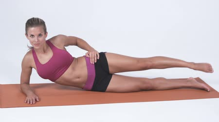 pozisyon : Full body shot of young woman laying on her side doing leg exercises. Shot in studio against a white background