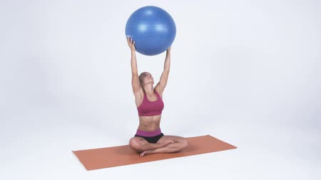 aerobik : Young woman sitting on a yoga mat lifts a yoga ball above her head. Shot in studio against a white background Stok Video