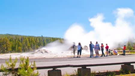 věrný : Time-lapse shot of Old Faithful Geyser in Yellowstone National Park, Wyoming. Tourists can be seen going near the geyser. The shot is a little blurry.
