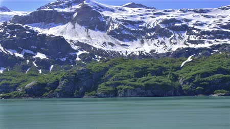 esquerda : Pan-left of a snowy, jagged mountain range with greenery covering rocks close to the shoreline.
