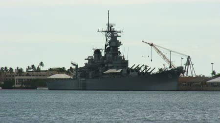 marynarka wojenna : Massive,iron,long,old,warship tanker with cannons and war equipment on board at dock at Pearl Harbor with construction equipment and american flag on its right and hotel and palm trees on left and ocean water on foreground Wideo