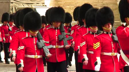 asker : British soldiers marching by in bearskin hats and red and black uniforms.