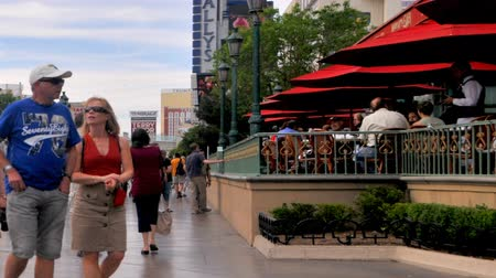 жир : Zooming timelapse Throngs of casually dressed tourists flood the Las Vegas Strip and a restaurant with umbrellas to the right.