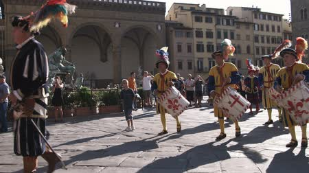 florencja : Wide shot of men in fancy attire playing instruments in a parade