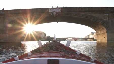 florencja : Wide shot going under bridge with sun flare from gondola pov