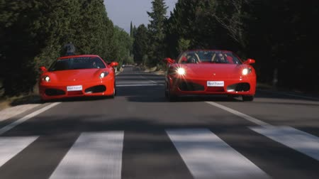 honit : Wide shot of two Ferraris driving on road