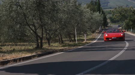honit : Wide shot of two ferraris driving by on country road