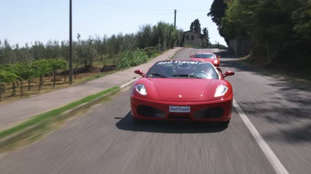 honit : Wide shot of two ferraris driving down country road