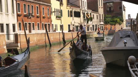 wenecja : Tourists in a gondola on a canal in Venice, Italy.