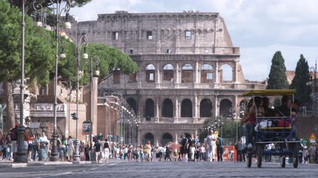 pro government : A shot of people pedaling a cart in from of the Coliseum in Rome Italy.
