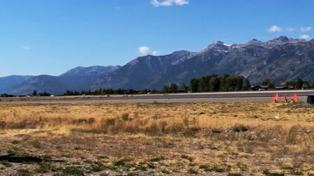 letadlo : Panning shot of airport at Jackson, Wyoming. The camera pans from right to left, first showing the mountains and then the airplane and buildings at the airport.