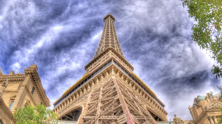 nevada : TImelapse, zooming to the top of the Paris Las Vegas Hotel and Casinos reproduction Eiffel Tower with flowing clouds in a blue sky.