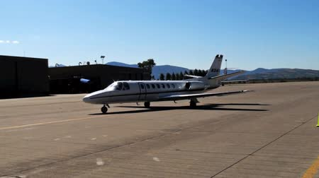 samoloty : On a tarmac, a lone Learjet turns and slowly taxis towards an airport hangar.